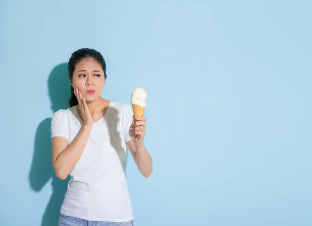 cute female student suffering sensitive tooth stock photo