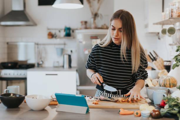 l'adolescente carina cucina la cena mentre fa una conversazione in videochiamata - cucinare foto e immagini stock