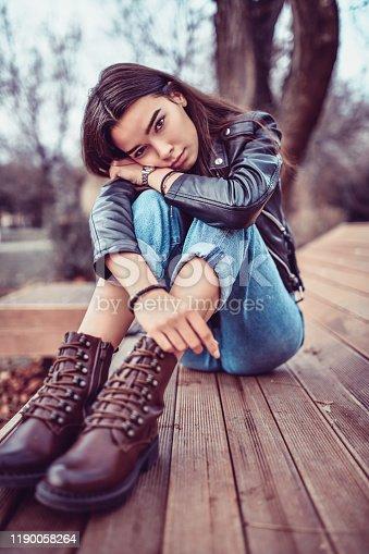 Cute Female Teenager Sitting On Pier Of Park Lake