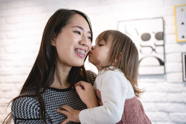 Cute female toddler kissing her mother in the cheek stock photo