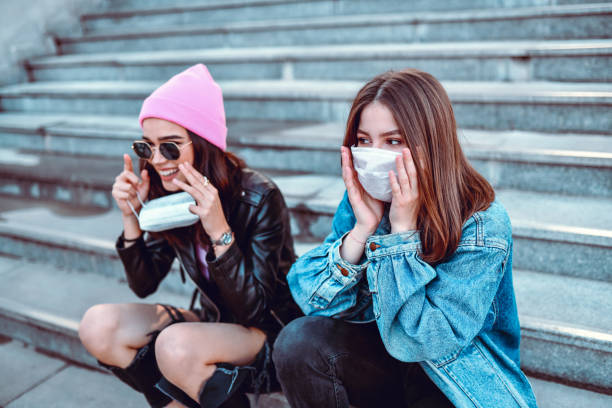 Cute Females Trying To Protect Themselves From Virus With Surgical Masks stock photo