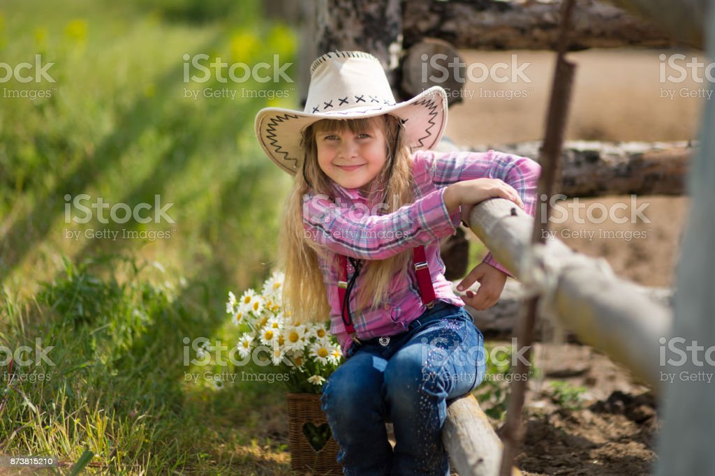 Cute fermer beautiful girl cowboy in jeans enjoying summer day in village life with flowers happyly smiling. stock photo