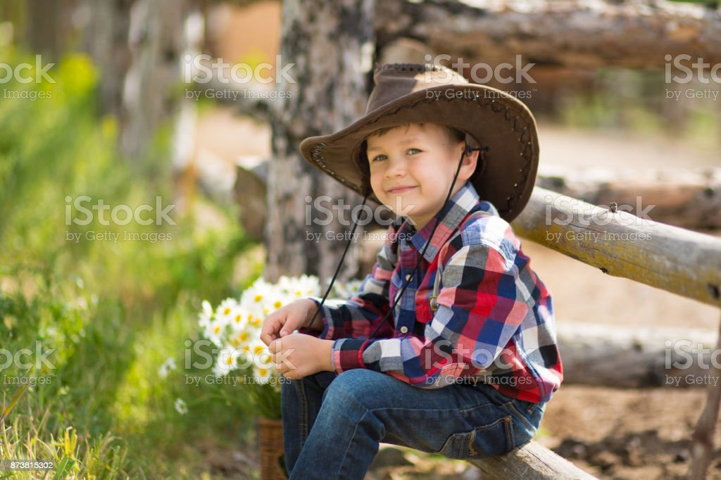 Cute fermer handsome boy cowboy in jeans enjoying summer day in village life with flowers wearing leather cow hat happyly smiling. stock photo
