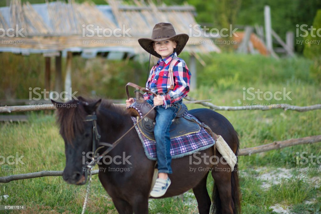 Cute fermer handsome boy cowboy in jeans enjoying summer day in village life with flowers wearing leather cow hat happyly smiling and sitting on horse . stock photo