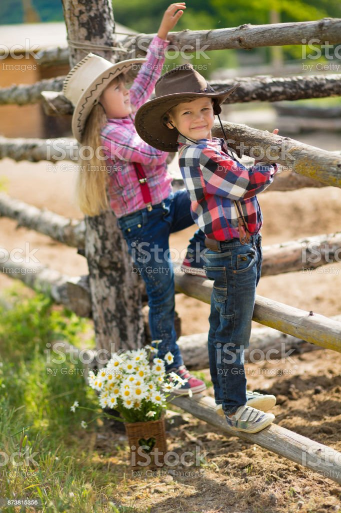 Cute fermer handsome boyand beautiful girl cowboy in jeans enjoying summer day in village life with flowers wearing leather cow hat happyly smiling. stock photo