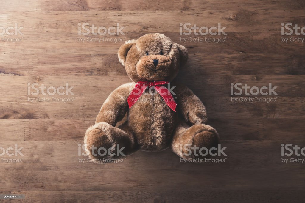 Cute fluffy smiling brown teddy bear toy on wood background stock photo
