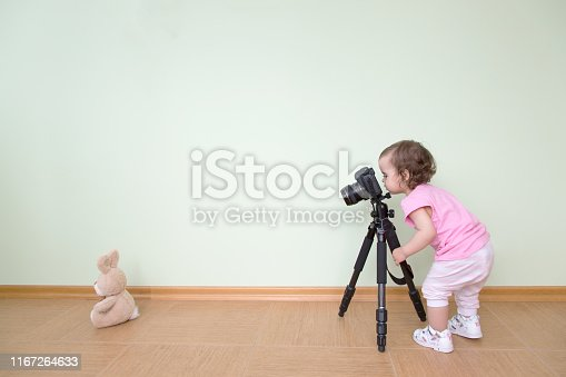 Cute funny beautiful baby in a pink T-shirt photographs her bunny. The baby stands and holds a DSLR camera on a tripod against the background of a green wall. Concept novice beginner photographer, first steps.
