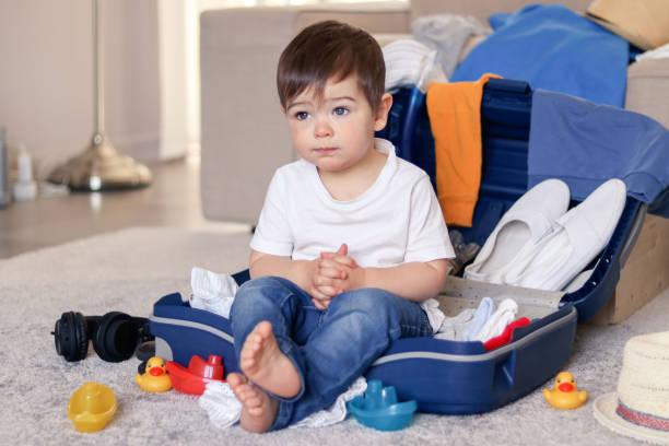 niedliche lustige kleine kleine junge, die sich in blauem koffer, müde von der verpackung von kleidung und spielzeug für den urlaub. machen sie sich bereit für reisen mit kind. tag träumen und an urlaub denken. - küstenfamilienzimmer stock-fotos und bilder