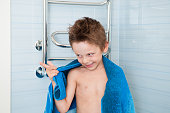 cute funny little boy with towel on his shoulders and wet hair in the bathroom