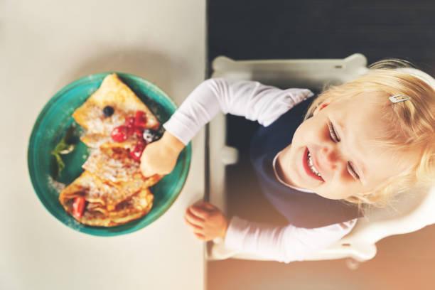 lustiges kleines Mädchen essen Pfannkuchen mit Beeren – Foto