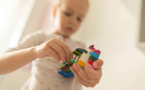 Cute funny preschooler little girl playing with construction toy stock photo