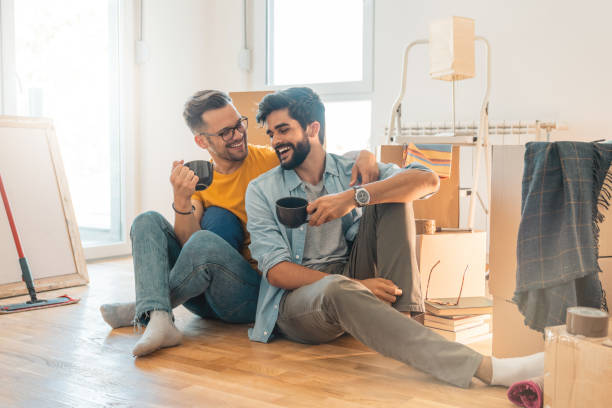 Cute gay couple sitting on floor and enjoying coffee in new home  - Stock image Cute gay couple sitting on floor and enjoying coffee in new home  - Stock image gay man stock pictures, royalty-free photos & images
