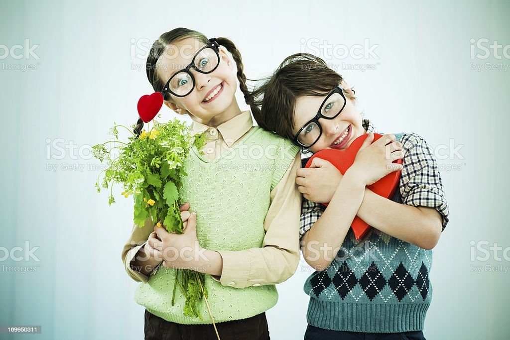 Cute geek boy and girl holding Valentine presents. stock photo