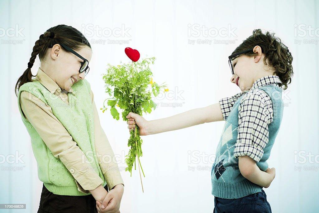 Cute geek boy giving his girlfriend a Valentine present. stock photo