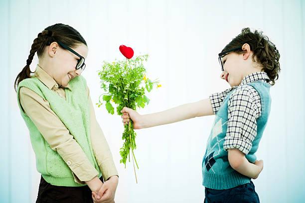 Adorable garçon geek donner sa petite amie un cadeau pour la Saint-Valentin. - Photo