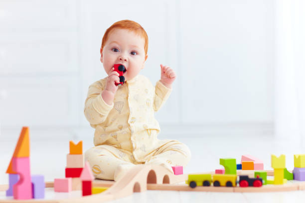 cute ginger baby playing with toy railway road at home. Tasting wagon stock photo