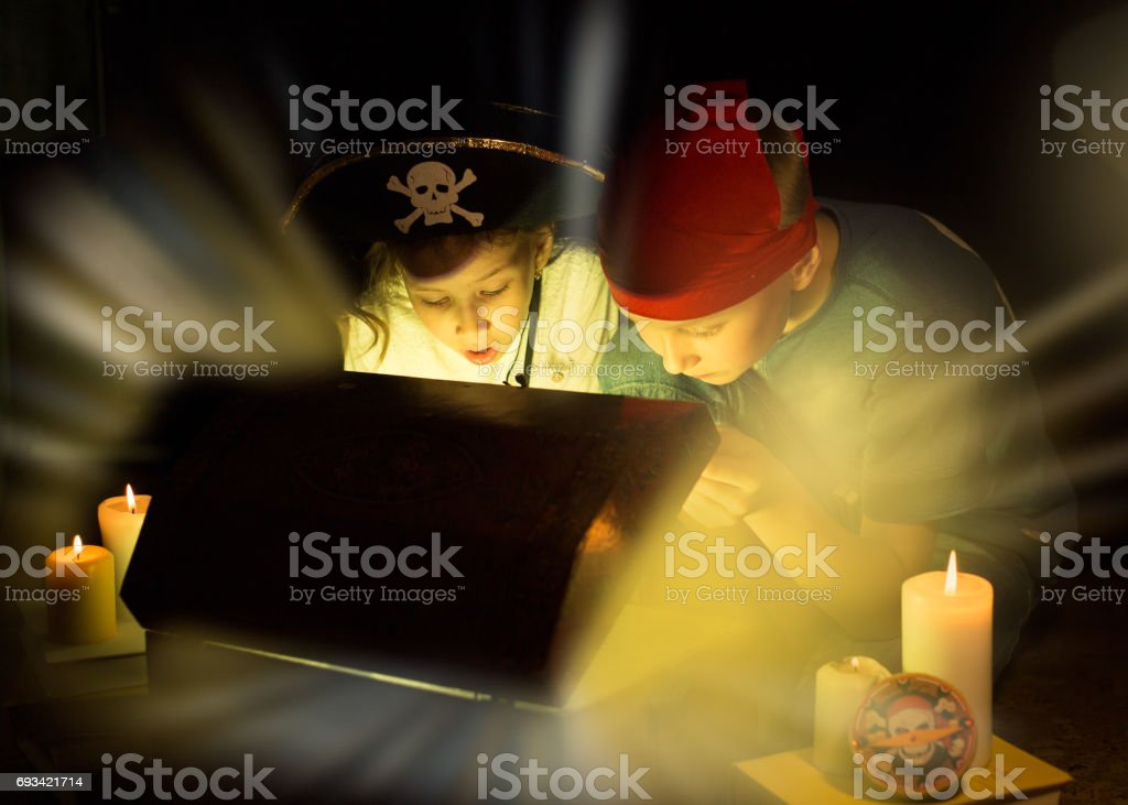 Cute girl and adventurous boy found a treasures. Happy young pirates. stock photo