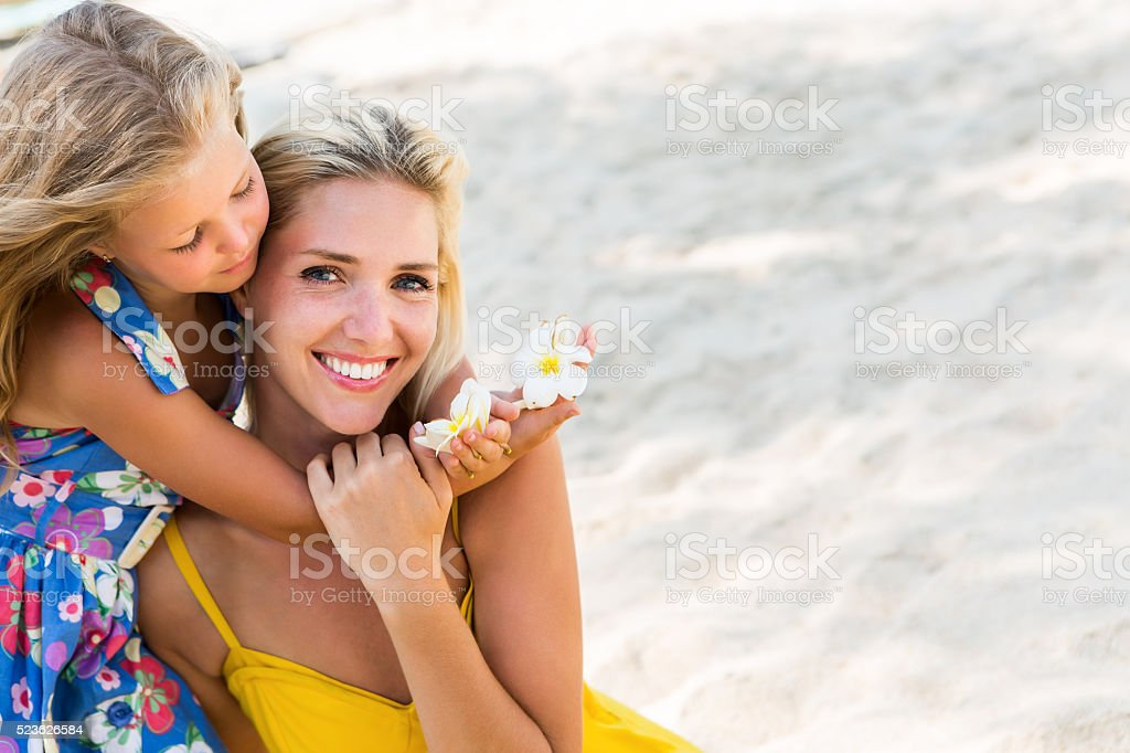 Cute girl and beautiful mother have fun on the beach. stock photo