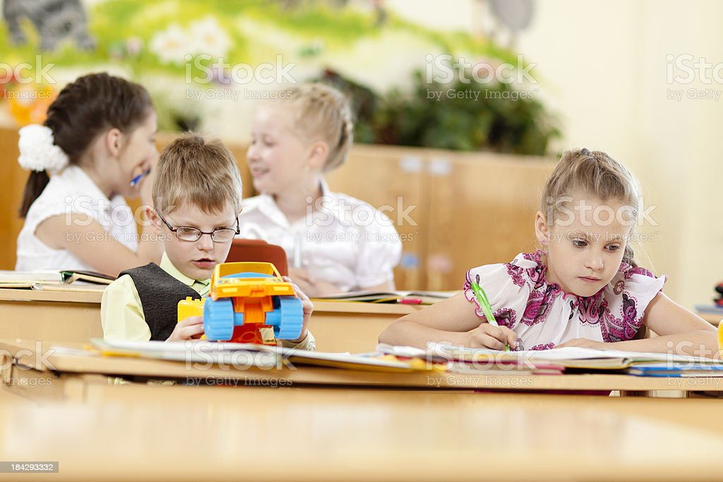 Cute girl and boy in the classroom stock photo