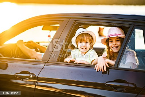 972962180istockphoto Cute girl and boy looking through the car window while traveling 1137633551