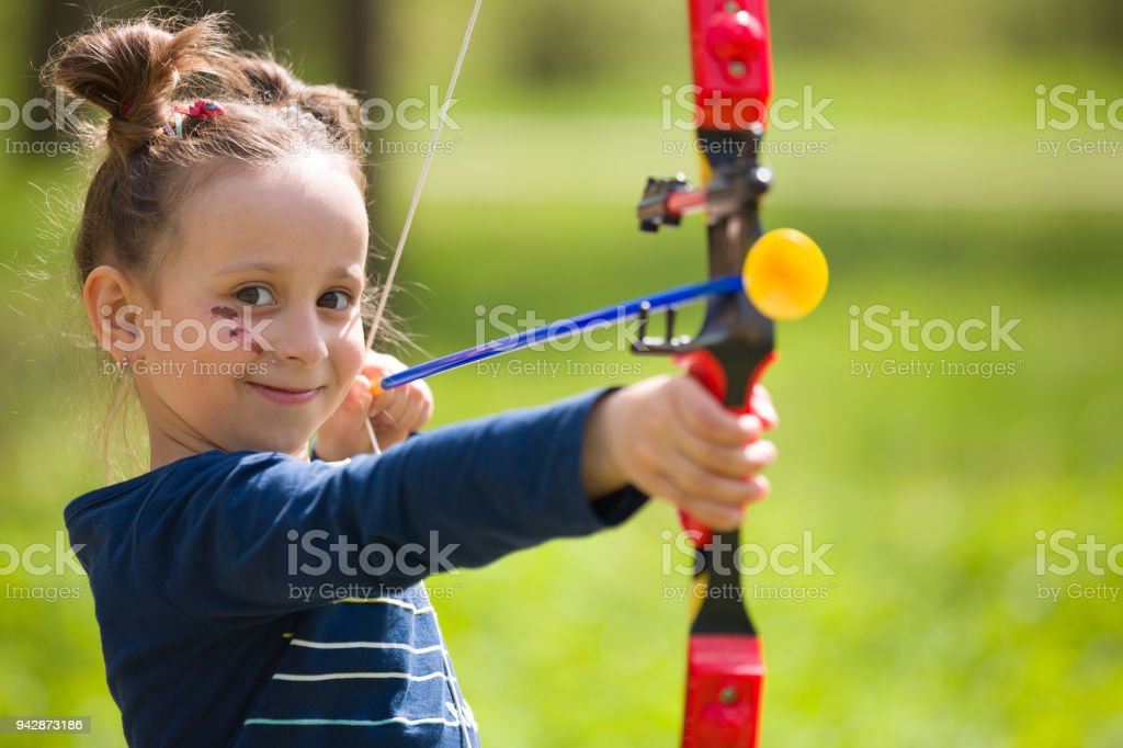 Cute girl archer with bow shooting in sunny summer day. little girl shoots bow in the park. Outdoors. Sport activities with children. Sport and lifestyle concept. Aiming high stock photo