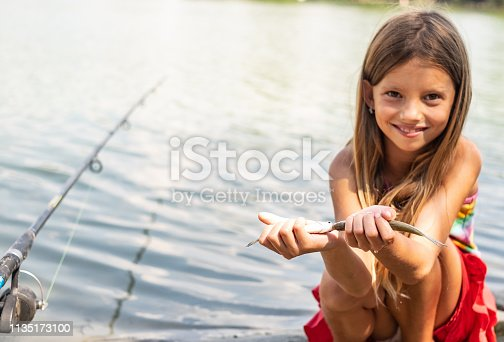 Cute little girl showing two small fish at the river bank