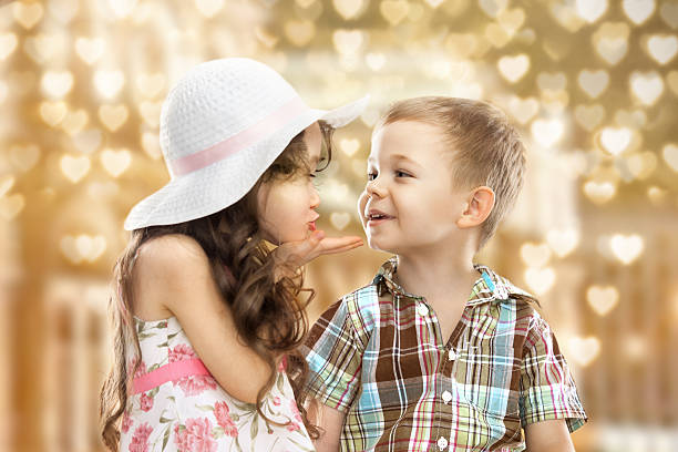 cute girl blowing a kiss to boy in heart bokeh background - little girls little boys kissing love stock photos and pictures