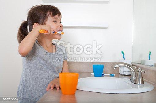 istock Cute girl brushing teeth 888672232