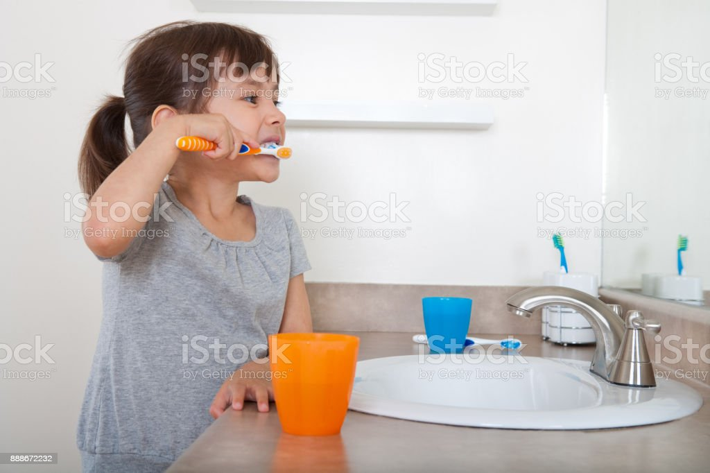 Cute girl brushing teeth stock photo