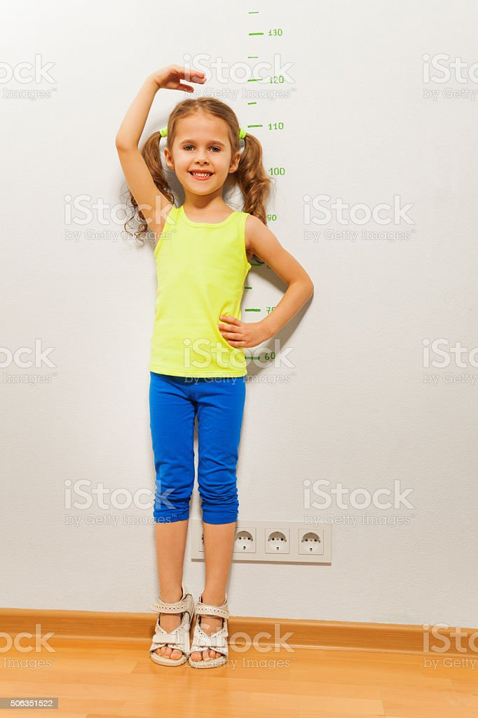 Cute girl checking height on wall with hand stock photo