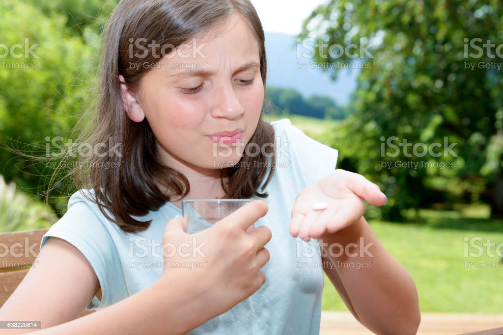 cute girl child taking pill with glass of water stock photo