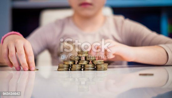 Close up little girl making a stucks of the coins at the table