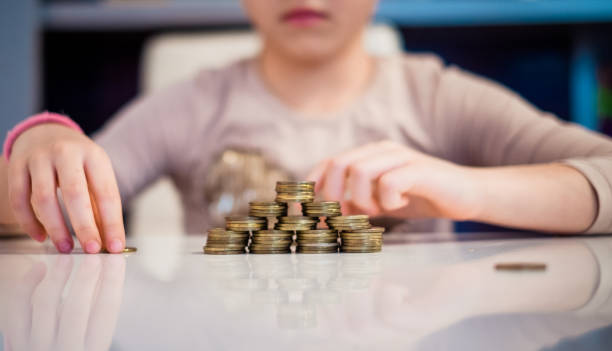 Cute girl counting a coins indoors Close up little girl making a stucks of the coins at the table allowance stock pictures, royalty-free photos & images