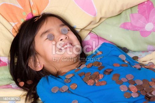 Chinese little girl lying down and covered with coins