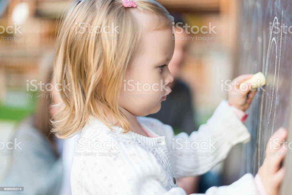 Nettes Mädchen auf Tafel zeichnen. Kleinkind Holding Kreide und Zeichnung. – Foto