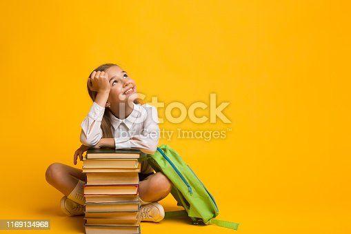 istock Cute Girl Dreaming About School Sitting With Backpack And Books 1169134968