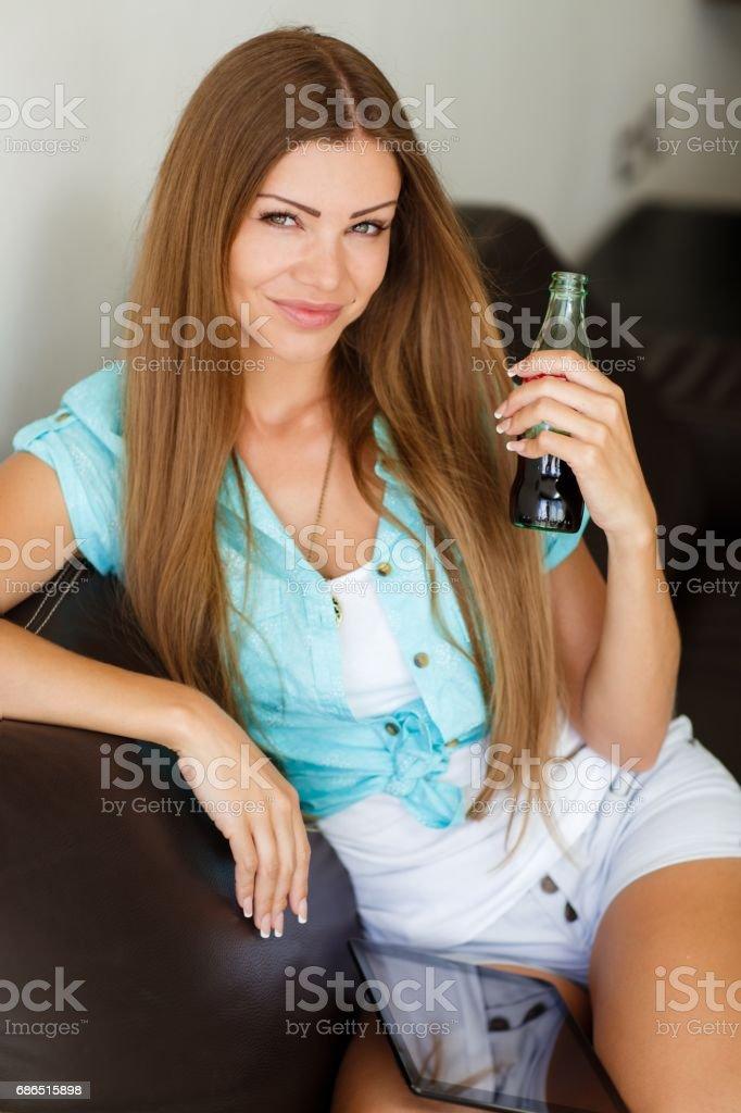 Söt tjej dricker Coca Cola från en flaska, sitter i soffan royaltyfri bildbanksbilder