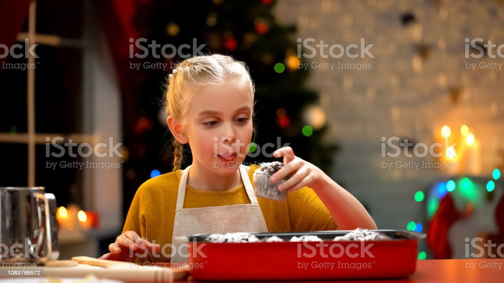 Cute girl eating chocolate muffin prepared for Christmas eve, holiday...