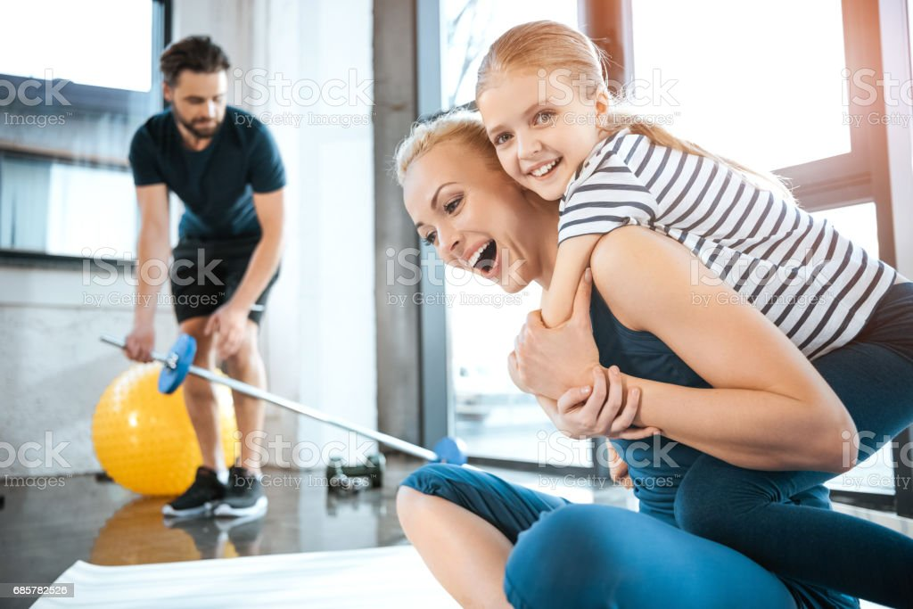 Cute girl embrace mother at fitness club royalty-free stock photo
