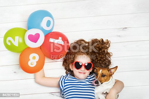 865399512istockphoto Cute girl embracing her puppy dog and holding rainbow balloons. 842921834