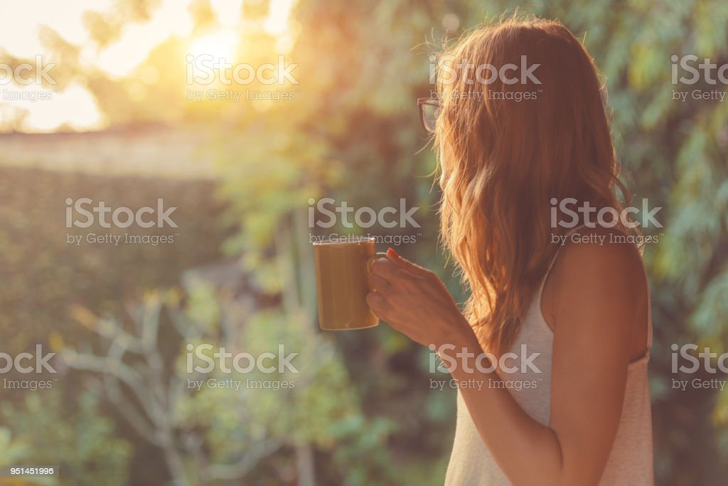 Cute girl enjoying morning coffee on the porch. stock photo