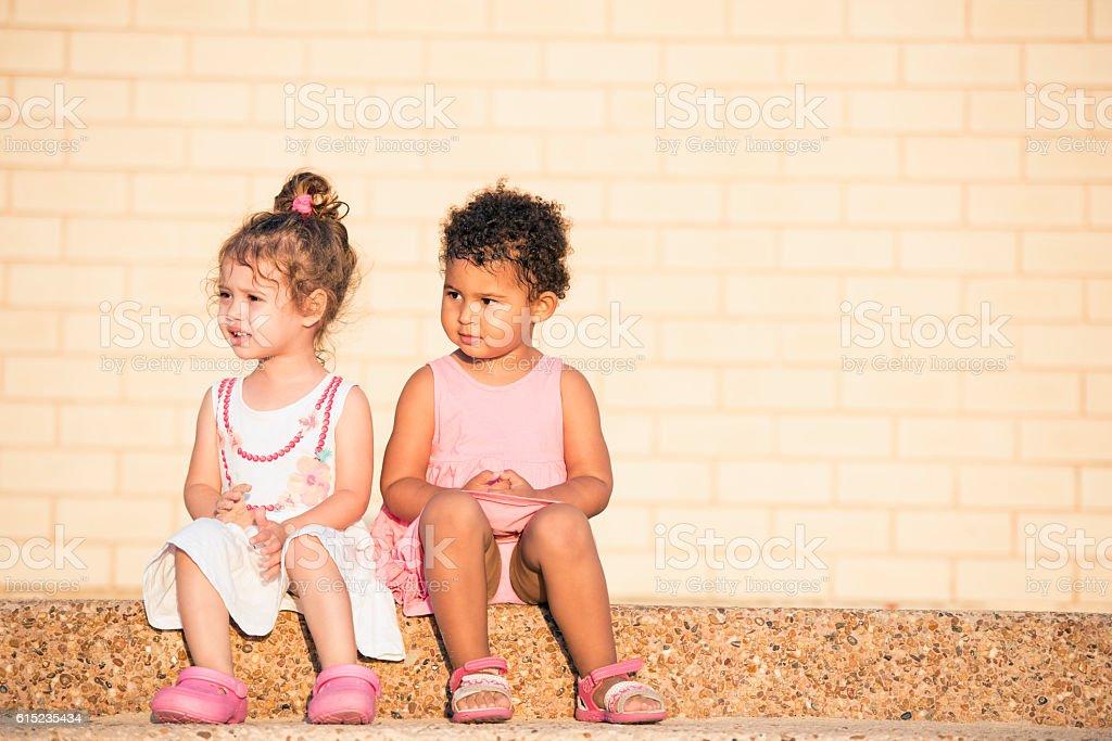 Cute girl friends sitting together. - foto de acervo