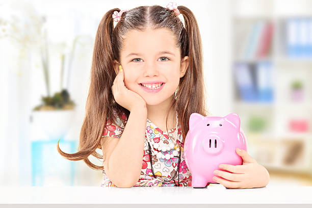 Cute girl holding a piggybank at home Cute girl sitting at table and holding her savings at home allowance stock pictures, royalty-free photos & images