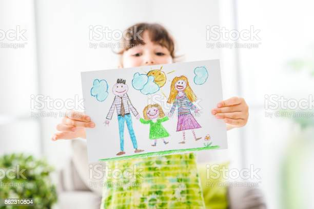 Cute young girl peeking behind a draw of her family, room interior on the background