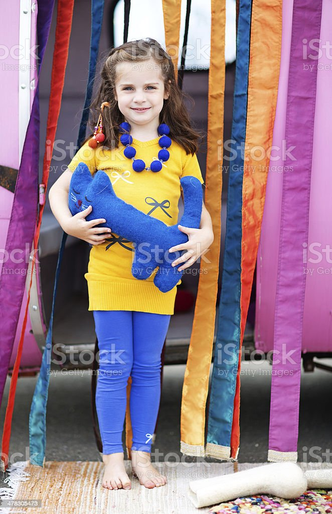 cute girl holding a toy cat posing against caravan royalty-free stock photo