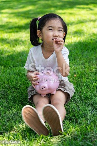 Cute Girl Holding An Pink piggy bank