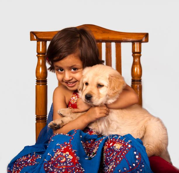 Cute girl holding Golden Retriever puppy