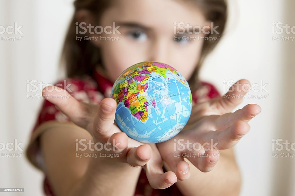 Cute girl holding little World Globe on her Hands stock photo