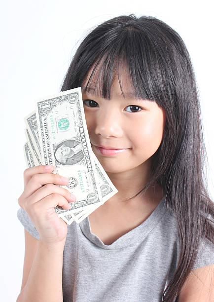 Cute girl holding money Cute girl holding money(dollar note) on white background. allowance stock pictures, royalty-free photos & images