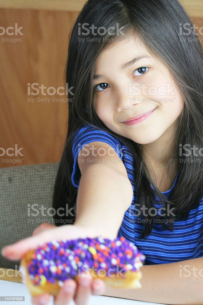 Cute girl holding up colorful donut royalty-free stock photo